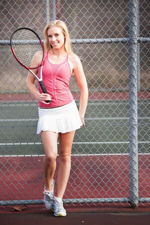 A beautiful caucasian tennis player on the tennis court photo