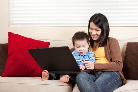 woman laptop happy: A portrait of a mother and a son using a laptop Stock Photo