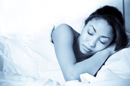 A shot of a sleeping black woman on her bed photo