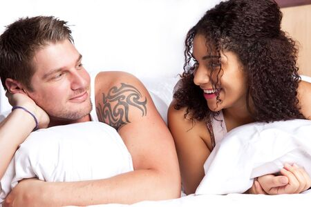 A portrait of a beautiful romantic interracial couple in love lying down on the bed photo