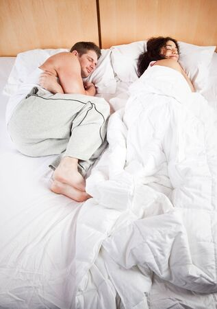 A shot of sleeping interracial couple on their bed photo