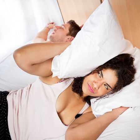 unable: A woman unable to sleep because of the snoring sound Stock Photo