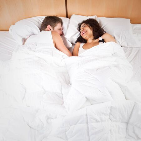 romance: A portrait of a beautiful romantic interracial couple in love lying down on the bed