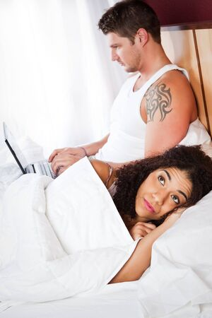 lovers in bed: A shot of an interracial couple having a relationship conflict Stock Photo