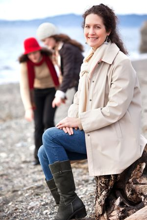 A portrait of a mother and her daughters on the beach photo
