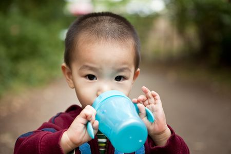 A portrait of an asian boy drinking from his cup photo