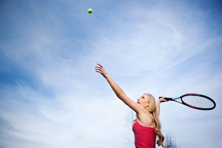A beautiful caucasian tennis player serving the ball on the tennis court photo