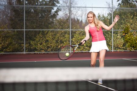 A beautiful caucasian tennis player hitting the ball on the tennis court photo