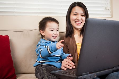 A portrait of a mother and a son using a laptop photo