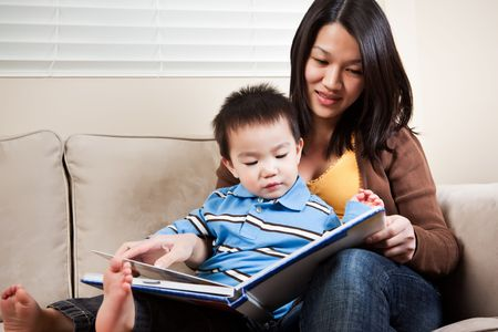 asian toddler: A portrait of a mother and a son reading a book