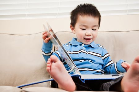 asian toddler: A portrait of an asian boy reading a book Stock Photo