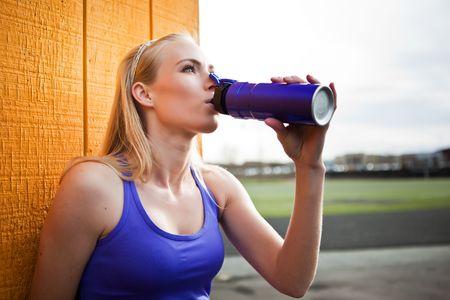 Een portret van een mooie sportief caucasian vrouw drinkwater