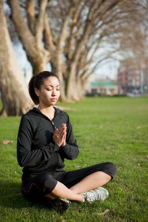 A beautiful black woman doing yoga meditation outdoor in a park Banco de Imagens