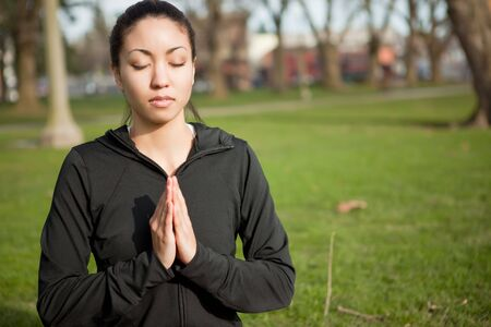 A beautiful black woman doing yoga meditation outdoor in a park photo