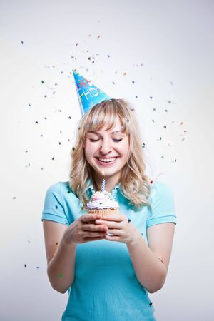 A shot of a girl celebrating her birthday holding a cupcake photo