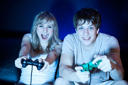 A shot of a young couple playing video games in the living room photo