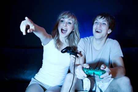 couple on couch: A shot of a young couple playing video games in the living room Stock Photo