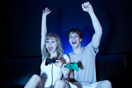 A shot of a young couple playing video games in the living room Stock Photo - 6681248