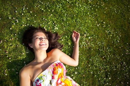 woman lying down: A portrait of a happy beautiful mixed race girl outdoor