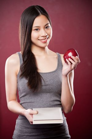 A shot of a beautiful asian college student carrying a book and an apple photo