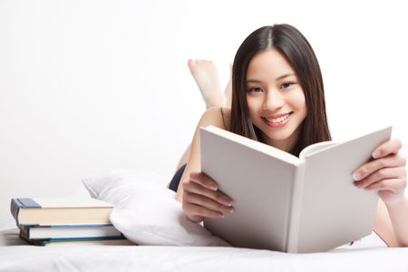 student reading: A shot of a beautiful asian college student reading on her bed
