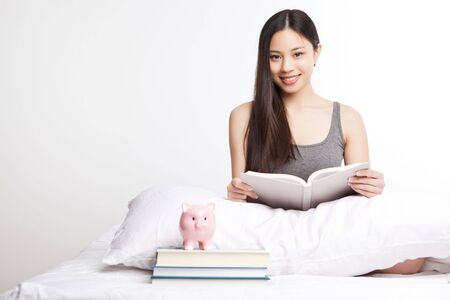 A shot of a beautiful asian college student reading on her bed photo