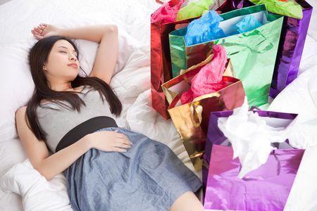 A shot of a beautiful asian girl sleeping on the bed after shopping Banco de Imagens
