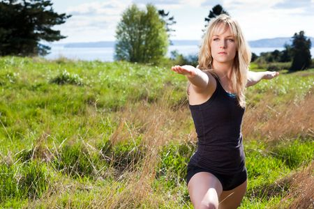 A beautiful caucasian woman practicing yoga outdoor in a park Imagens