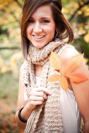A portrait of a beautiful caucasian holding an autumn leaf photo