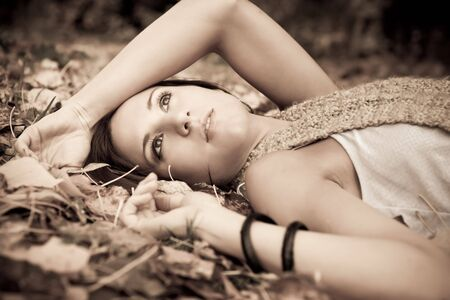 A portrait of a beautiful caucasian woman lying down on autumn leaves on the ground photo
