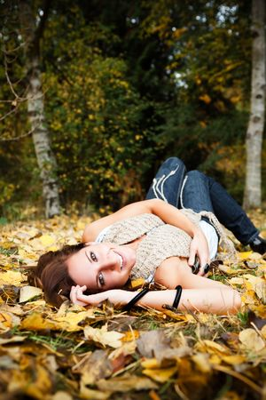 A portrait of a happy beautiful caucasian woman lying down on autumn leaves on the ground photo