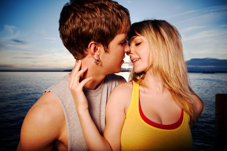 A shot of a young caucasian couple kissing outdoor