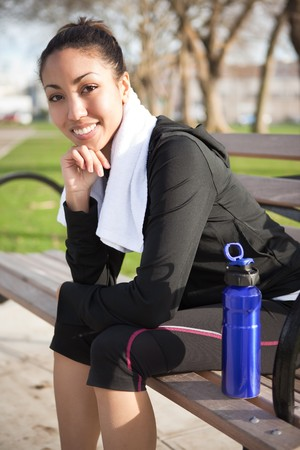 A beautiful black woman sitting on a park bench after exercise photo