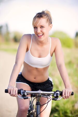 A sporty woman riding a bicycle outdoor photo