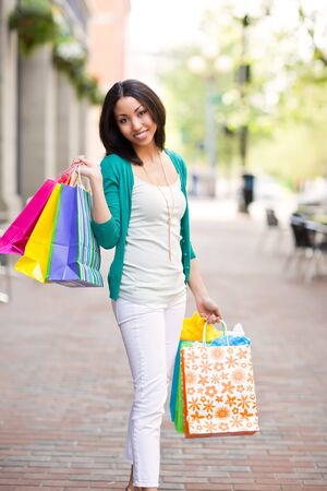 A shopping black woman carrying shopping bags outdoor Stock Photo - 7013162