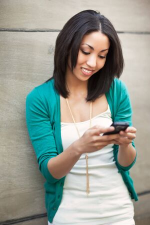 mobile communication: A beautiful black woman texting on her phone Stock Photo