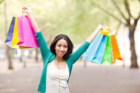 A shopping black woman carrying shopping bags outdoor