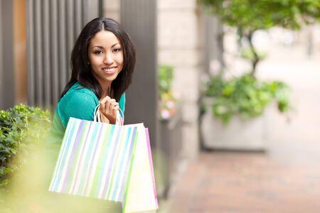A shopping black woman carrying shopping bags outdoor photo