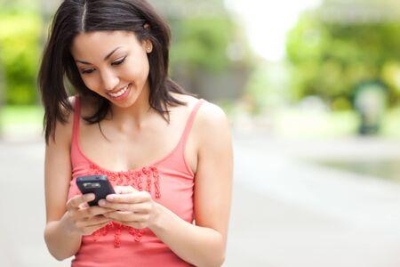 Un disparo de un texto de mujer de raza mixta en su teléfono celular Foto de archivo - 7213440