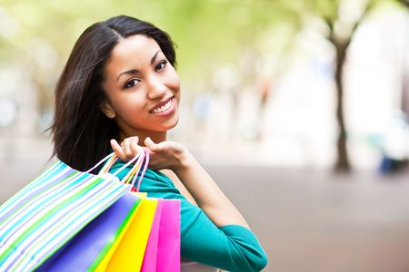 happy shopper: A shopping black woman carrying shopping bags outdoor
