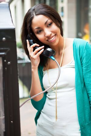 A beautiful black woman talking on the public phone Stock Photo - 7250060