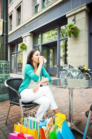 sipping: A shopping black woman resting at a cafe after shopping Stock Photo
