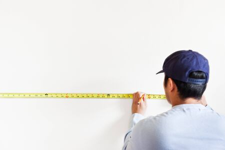 A shot of a man using measurement tape for home improvement photo