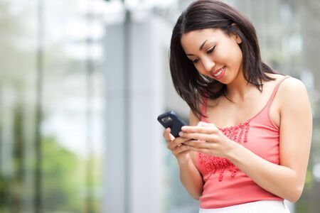 A shot of a mixed race woman texting on her cell phone Stock Photo - 7309583
