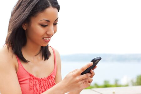 A shot of a mixed race woman texting on her cell phone photo