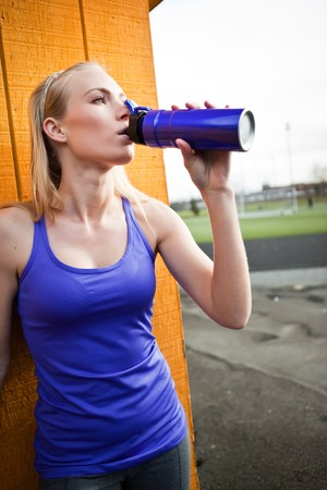 A portrait of a beautiful sporty caucasian woman  drinking water photo