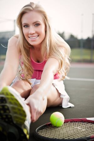 A beautiful caucasian tennis player stretching on the tennis court photo