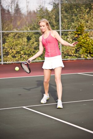 jugando tenis: Una hermosa tenista cauc�sicos golpear la bola en la cancha de tenis