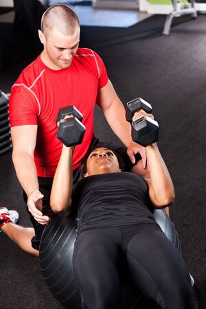 trainer: A shot of a male personal trainer assisting a woman lifting weights