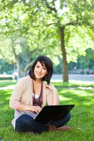 Mixed race college student sitting on the grass working on laptop at campus photo